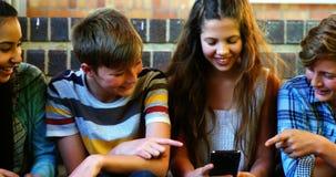Estudiantes sonrientes de la escuela que se sientan en la escalera usando el teléfono móvil almacen de video