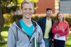 Estudiantes sonrientes delante de la escuela Imagenes de archivo