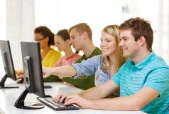 Estudiantes sonrientes en clase del ordenador en la escuela Fotos de archivo
