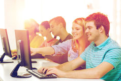Estudiantes sonrientes en clase del ordenador en la escuela Foto de archivo libre de regalías