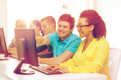 Estudiantes sonrientes en clase del ordenador en la escuela Imagenes de archivo