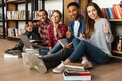 Estudiantes sonrientes jovenes que se sientan en la biblioteca que muestra los pulgares para arriba Fotos de archivo