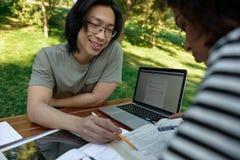 Estudiantes sonrientes jovenes que se sientan y que estudian al aire libre Fotografía de archivo libre de regalías