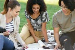 Estudiantes sonrientes que estudian al aire libre Mirada a un lado Fotos de archivo libres de regalías