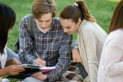 Estudiantes sonrientes que estudian al aire libre Mirada a un lado Foto de archivo libre de regalías