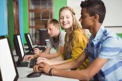 Estudiantes sonrientes que estudian en sala de clase del ordenador Fotografía de archivo