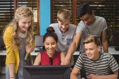 Estudiantes sonrientes que estudian en sala de clase del ordenador Foto de archivo