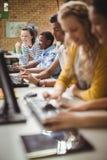 Estudiantes sonrientes que estudian en sala de clase del ordenador Imagen de archivo