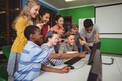 Estudiantes sonrientes que estudian junto en sala de clase del ordenador Fotos de archivo libres de regalías
