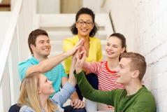 Estudiantes sonrientes que hacen la sentada del gesto del alto cinco Imagen de archivo libre de regalías