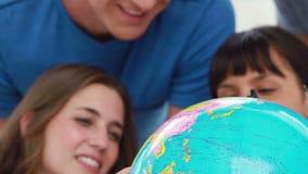 Estudiantes sonrientes que miran el mundo en un globo almacen de video