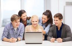 Estudiantes sonrientes que miran el ordenador portátil la escuela Foto de archivo libre de regalías