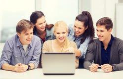 Estudiantes sonrientes que miran el ordenador portátil la escuela Imagenes de archivo