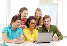 Estudiantes sonrientes que miran el ordenador portátil la escuela Fotografía de archivo
