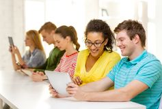 Estudiantes sonrientes que miran la PC de la tableta la escuela imagen de archivo