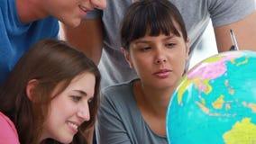 Estudiantes sonrientes que señalan en los países en un globo metrajes