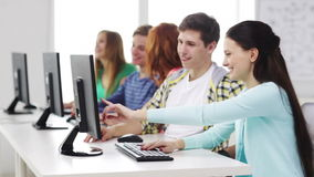 Estudiantes sonrientes que trabajan con los ordenadores en la escuela almacen de metraje de vídeo