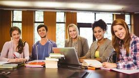 Estudiantes sonrientes que trabajan junto en una asignación Fotografía de archivo