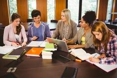 Estudiantes sonrientes que trabajan junto en una asignación Imagen de archivo