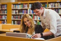 Estudiantes sonrientes que trabajan junto mientras que se sienta en la tabla fotografía de archivo