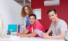 Estudiantes sonrientes que usan el ordenador y la tableta junto Imagenes de archivo