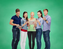 Estudiantes sonrientes que usan smartphones y la PC de la tableta Fotografía de archivo libre de regalías