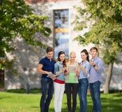 Estudiantes sonrientes que usan smartphones y la PC de la tableta Imagen de archivo libre de regalías