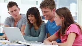 Estudiantes sonrientes que usan un ordenador portátil junto almacen de metraje de vídeo