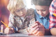 Estudiantes talentosos productivos que leen las notas cuidadosamente Fotografía de archivo libre de regalías
