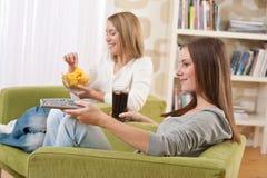 Estudiantes - televisión de observación del adolescente de dos hembras Imagen de archivo