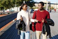 estudiantes universitarios alegres que caminan en campus Imagen de archivo libre de regalías
