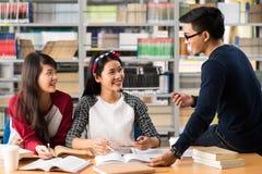 Estudiantes universitarios asiáticos en biblioteca Imagen de archivo