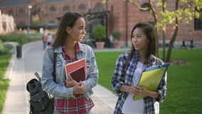 Estudiantes universitarios asiáticos y caucásicos que caminan en campus y que hablan de la educación metrajes