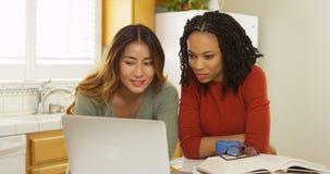 Estudiantes universitarios asiáticos y negros que estudian con el ordenador portátil Fotos de archivo