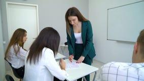 Estudiantes universitarios caucásicos jovenes conocimiento y habilidades del chek y del control del profesor en sala de clase almacen de metraje de vídeo