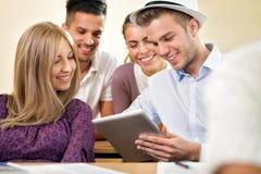 Estudiantes universitarios con la tableta junto Imagen de archivo