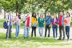 Estudiantes universitarios con los bolsos y libros que se colocan en parque Imagen de archivo libre de regalías