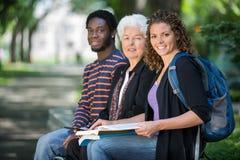 Estudiantes universitarios confiados que se sientan en campus Foto de archivo libre de regalías