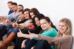 Estudiantes universitarios confiados que se sientan en fila Foto de archivo libre de regalías
