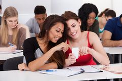 Estudiantes universitarios de sexo femenino felices que usan el teléfono móvil junto Fotografía de archivo libre de regalías
