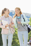 Estudiantes universitarios de sexo femenino jovenes alegres que caminan en campus Foto de archivo libre de regalías