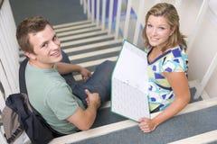 Estudiantes universitarios de sexo masculino y de sexo femenino que se sientan en las escaleras Imagenes de archivo