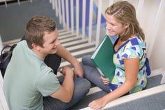 Estudiantes universitarios de sexo masculino y de sexo femenino que se sientan en las escaleras Imágenes de archivo libres de regalías