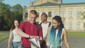 Estudiantes universitarios diversos que caminan en campus universitario almacen de metraje de vídeo