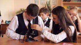 Estudiantes universitarios en el microscopio del funcionamiento del uniforme escolar que se sienta en la sala de clase El concept almacen de video