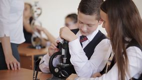 Estudiantes universitarios en el microscopio del funcionamiento del uniforme escolar que se sienta en la sala de clase El concept metrajes