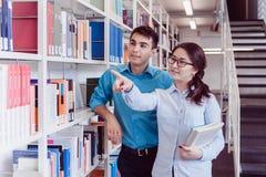 Estudiantes universitarios en la biblioteca que busca un libro Imagen de archivo
