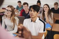 Estudiantes universitarios en la clase vista de detrás profesor imagenes de archivo