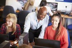 Estudiantes universitarios en los ordenadores en clase de la tecnología Fotos de archivo