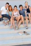 Estudiantes universitarios felices que se sientan el verano de las escaleras Imagen de archivo libre de regalías